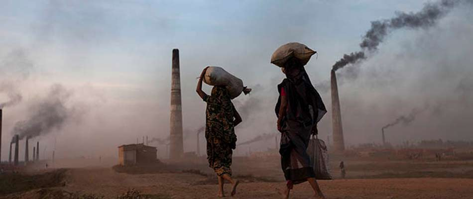Two women from Bangladesh walking through the acrid air surrounding a coal burning power plant.
